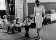 Ring bearer and Small children with cart being lead by Mom into the wedding ceremony