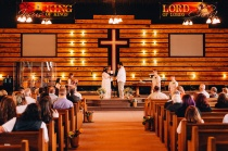 Bride and Groom exchanging vows at church before crowd of sitting people