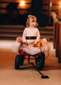 Little Girl standing on small cart at wedding ceremony