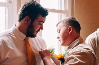 Young Groomsmen fixes boutonniere of Groom by the window, Moody candid Wedding Portrait