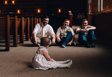 Groom, Groomsmen and Little sister at front looking at them in the church, wedding portrait