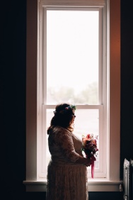 Wedding picture of Bride, her Bouquet being framed within a window with light in the back and around her