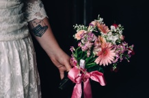 Portrait of Bride holding Bouquet while showing awesome Tattoo
