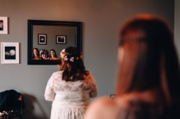 Bride looking at her bridesmaids through a mirror's reflection