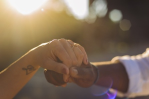 Couple hold hands while sunlight comes in at Golden Hour