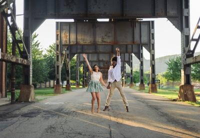 Couple Jumping under a Bridge While Sun Shines Through