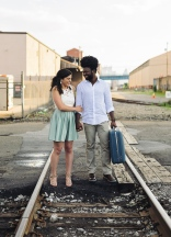 Engagement Portrait of Couple looking at each other smiling on railroad trails