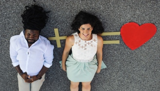 Portrait of Couple laying on the ground with a plus sign equals love