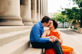 Couple kissing in a engagement session while sitting