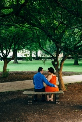 Cute Portrait of Couple sitting in a bench underneath trees while holding hands