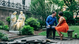 Couple looking at each other romantically in a park next to a statue