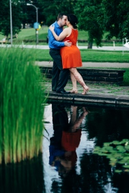 Couple kissing for a Portrait next to a pond while their reflection is in the water