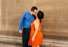 Portrait of Couple leaning against a wall while kissing