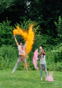 Portrait Of Engaged Couple Jumping in the Air with Colorful Paint