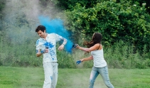 Woman throwing powder paint at fiance's face