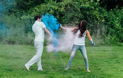 Couple throwing paint at each other at engagement session