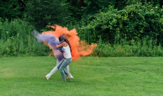 Couple throwing paint at each other while running at engagement session a