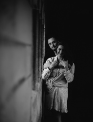 By the window light black and white portrait of couple smiling and holding each other while looking at the camera