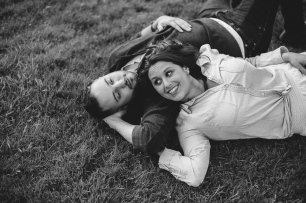 Black and White Portrait of man and woman smiling at each other while laying on the grass