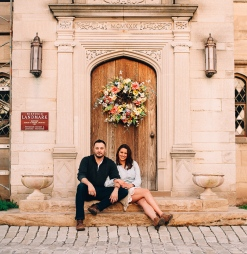 Lovely Portrait of man and woman sitting by a door while smiling at the camera