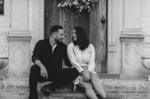 Black and White Portrait of couple looking extremely happy at each other while sitting by a door