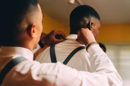 Groomsmen fixing groom's tie