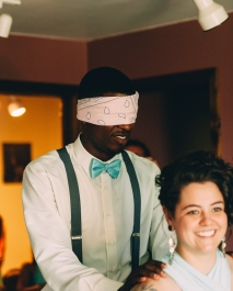 Portrait of Groom being led to bride blindfolded