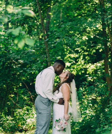 Portrait of Bride and Groom kissing under a canopy of trees