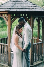 Portrait of Groom kissing Bride's forehead in front of gazebo