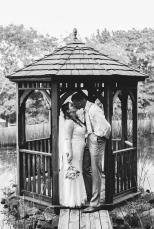 Black and White Portrait of Bride and Groom kissing under gazebo next to a lake