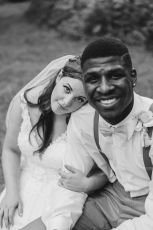 Black and White Portrait of Bride and Groom looking at camera while Bride rests her head on Grooms shoulder