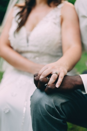 Portrait of Bride and Groom holding hands while rings are in focus