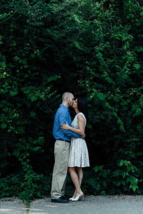 Portrait of man and woman kissing in front of wall tree in a engagement portrait session