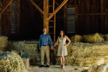 Portrait of man and woman holding hands in a barn during an engagement session
